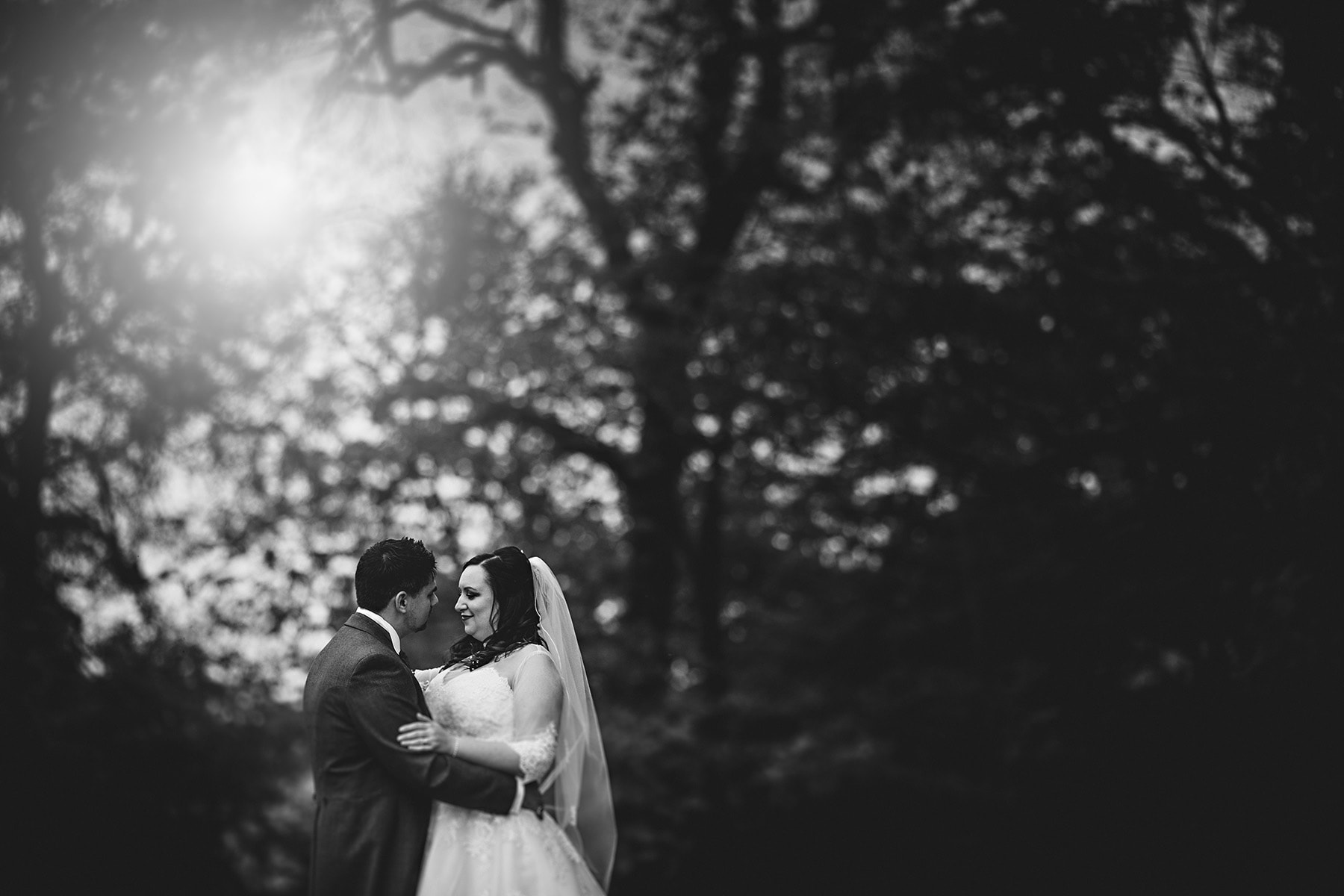 the bride and groom stood in aongst the trees in black and white