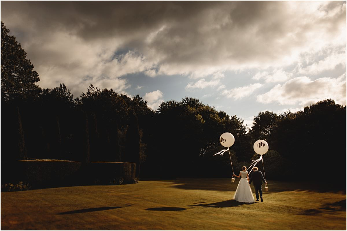 the bride & groom walking in golden hour at Newton House Barns