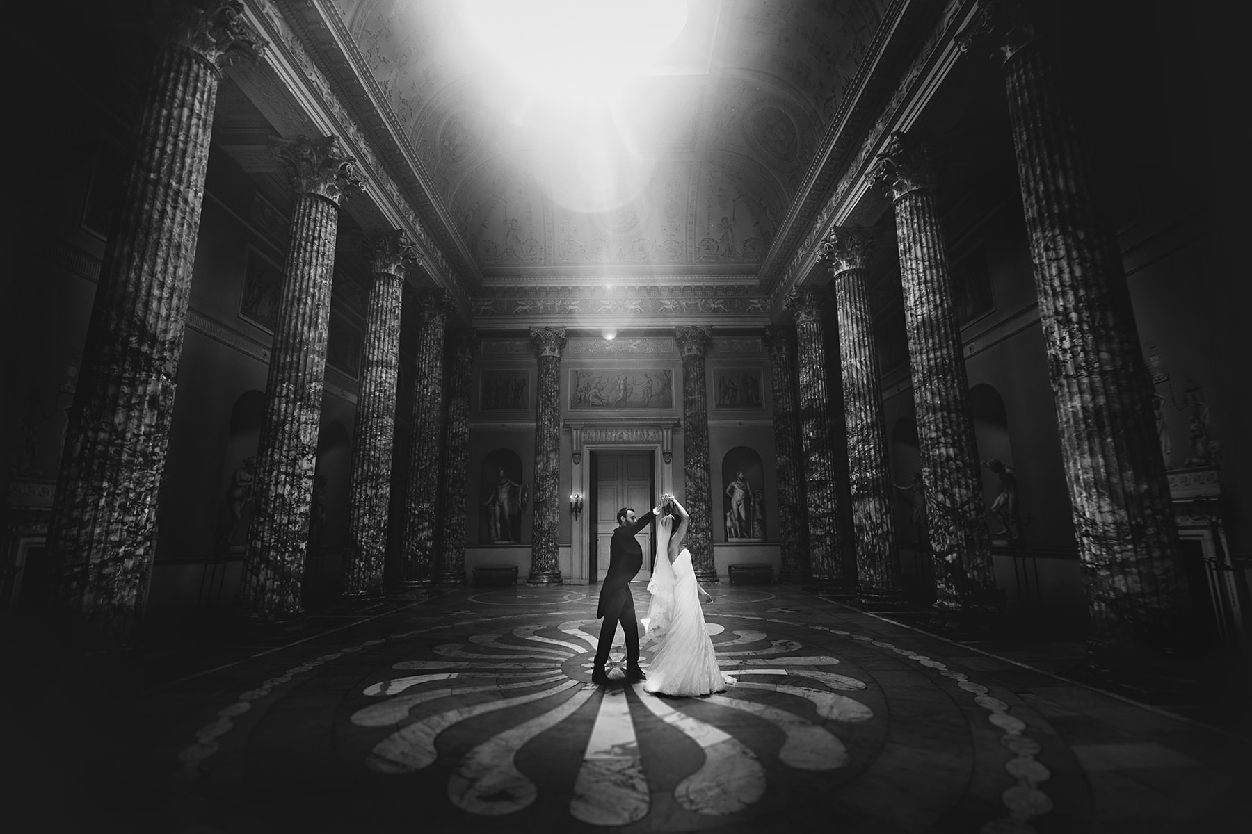 a black and white photo of the bride and groom at kedleston hall on their wedding day