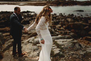bride and groom walking on the beach on Guernsey on thier wedding day