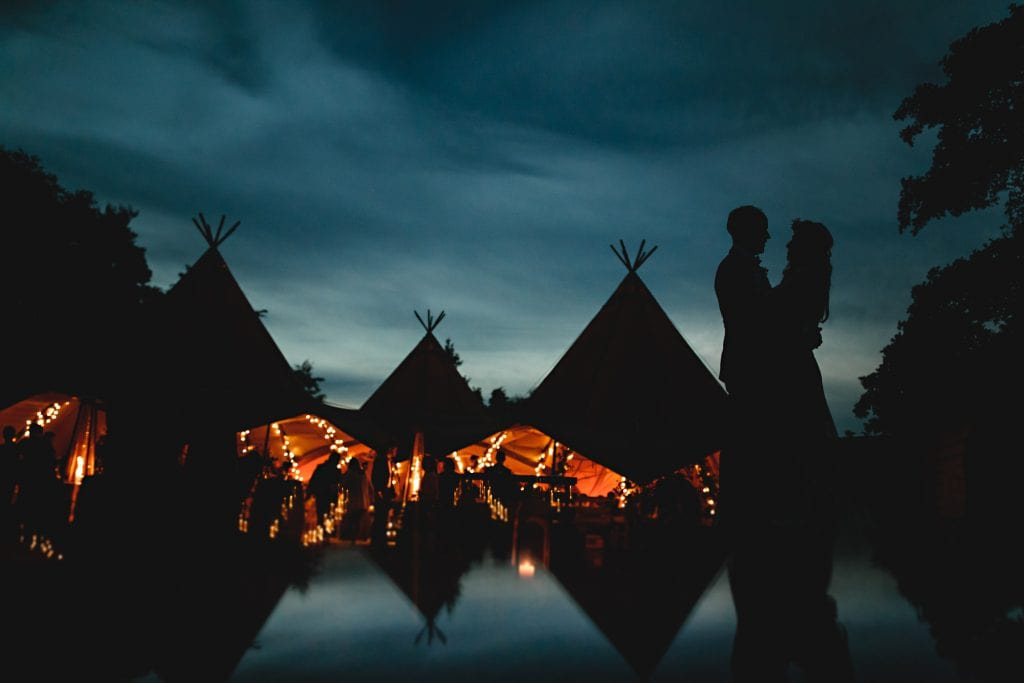 tipi wedding with alternative bride and groom against the blue sky and the dark tipi