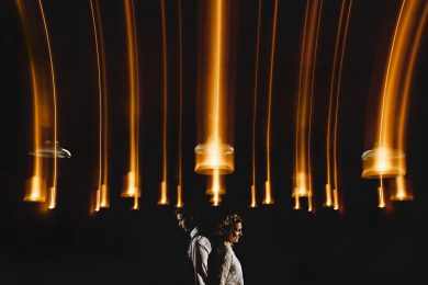 the bride and groom stood in orange light at The West Mill Wedding Venue