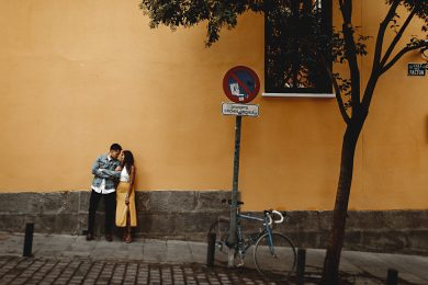 the bride and groom against a yellow wall in the streets of Madrid, spain