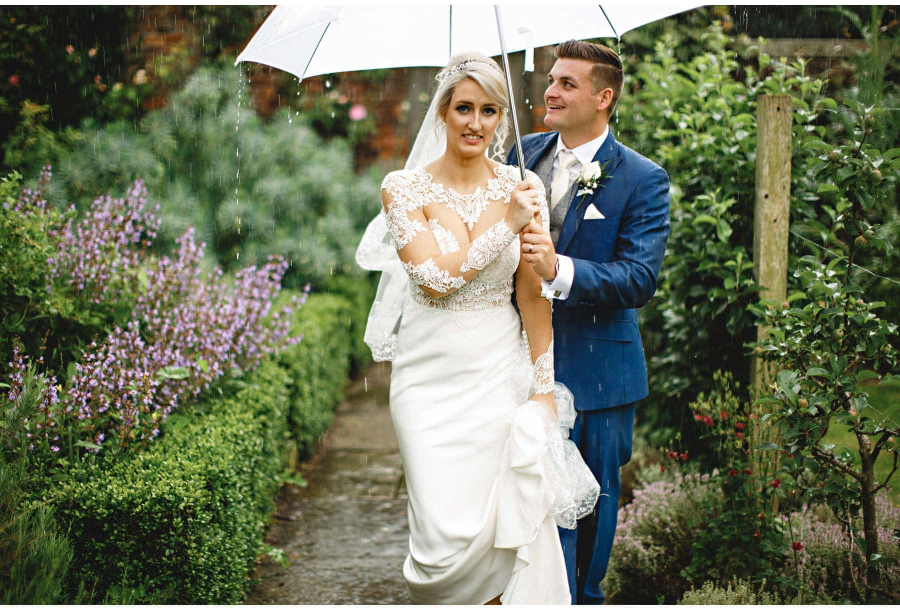 the bride and groom walking in the rain