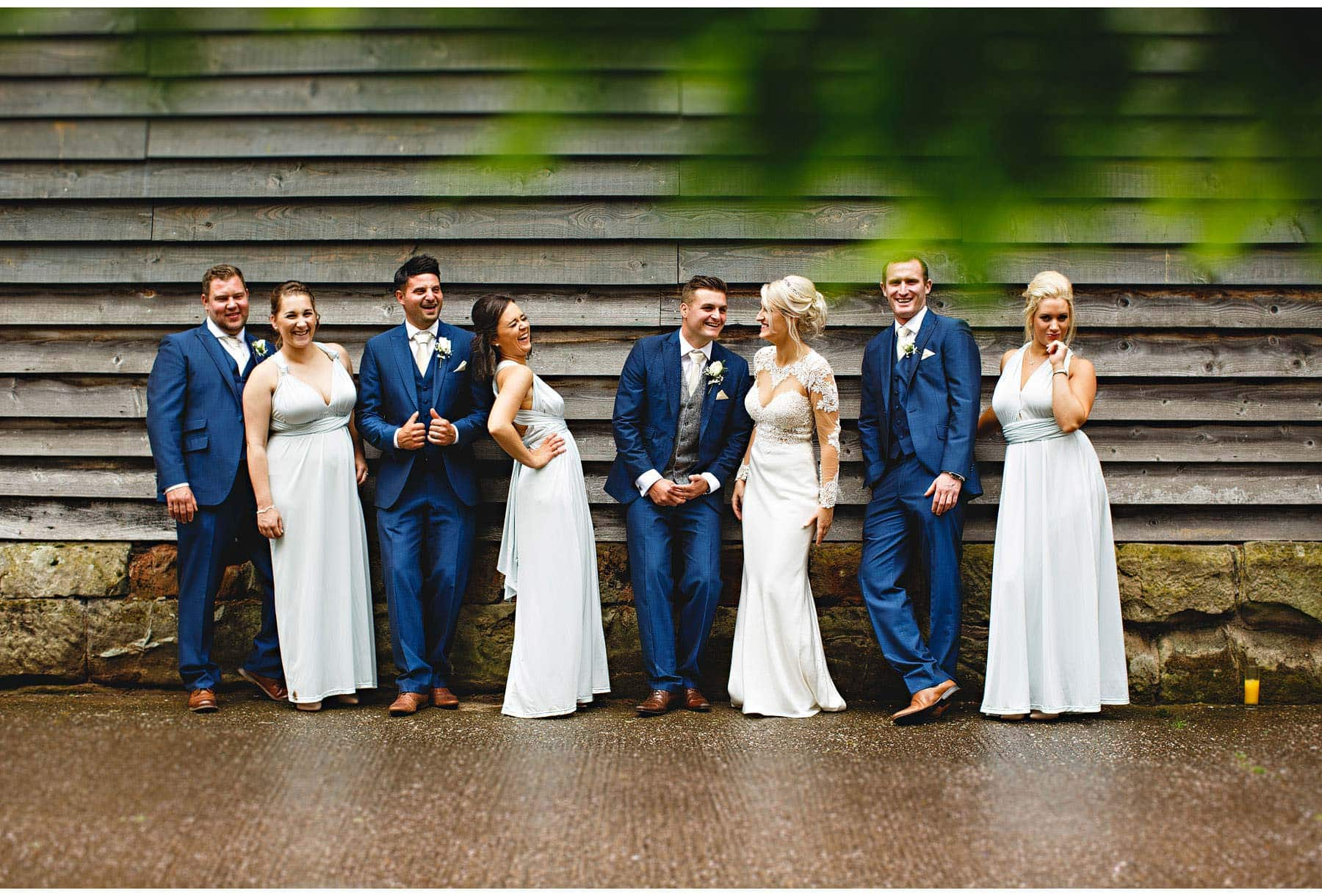 The bridal party leaning against the barn