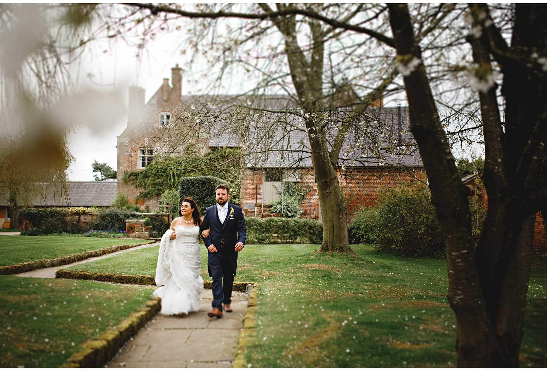 the bride and groom walking away from the main house