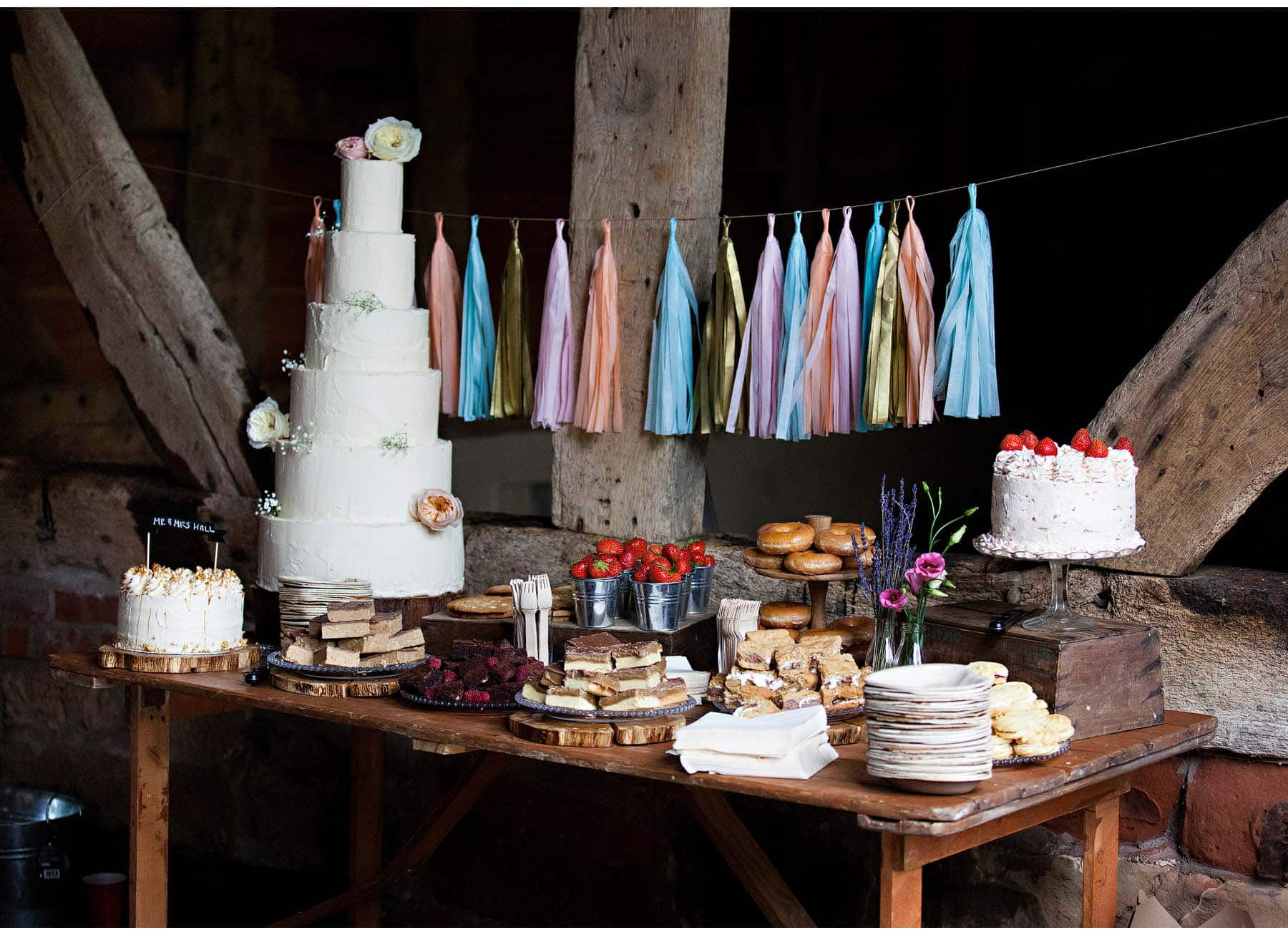 The wedding cake table, with doughnuts, brownies and strawberries