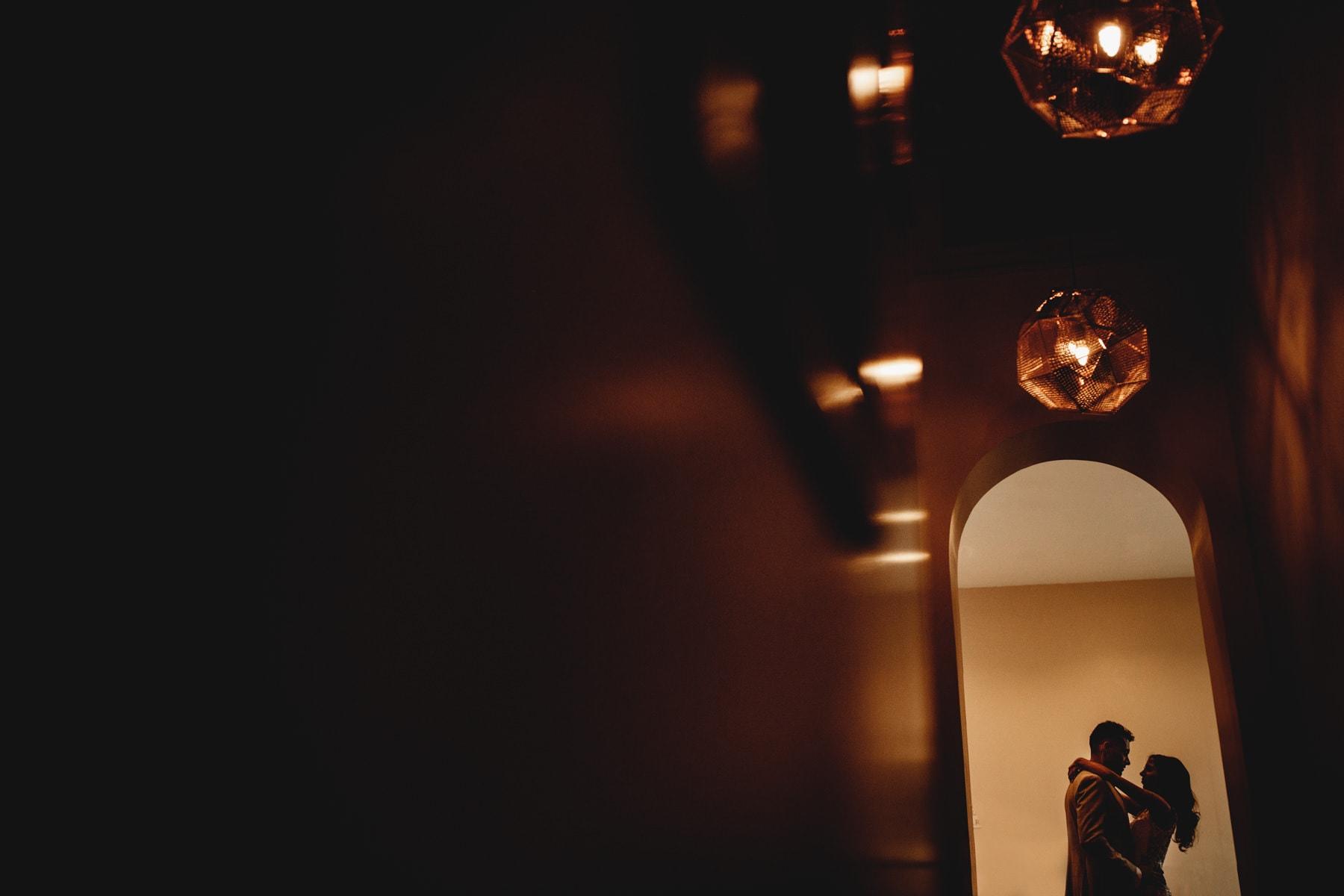 bride and groom in orange doorway under lights for wedding photos at winstanley house