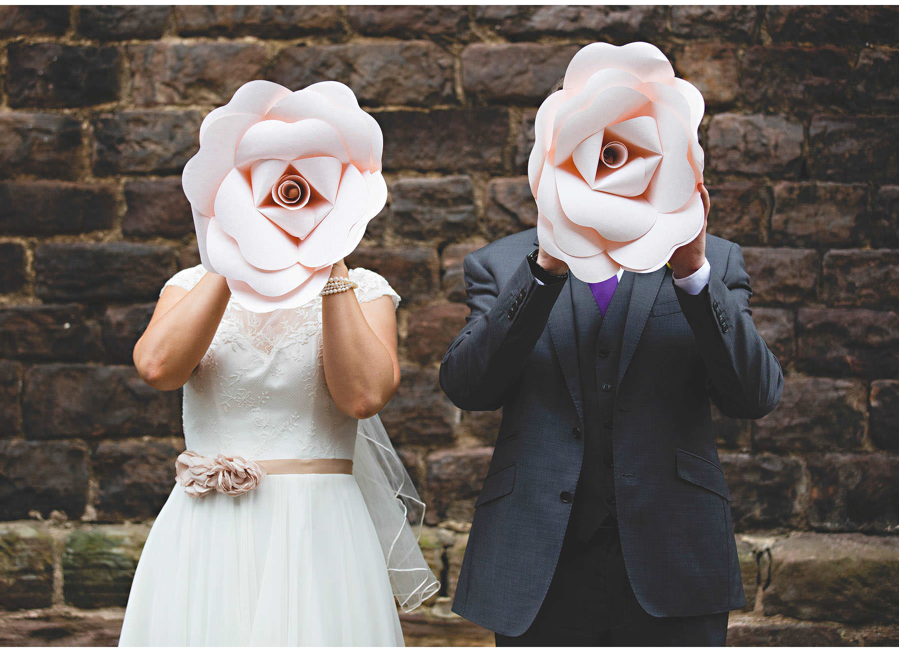 The bride & groom hiding behind giant paper flowers