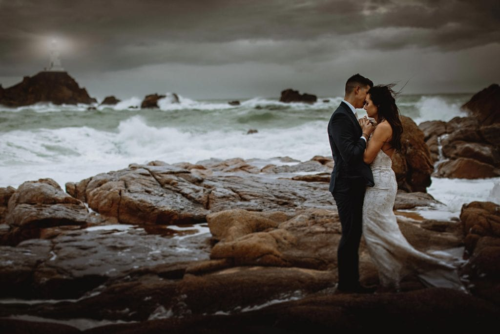 The bride and groom stood on the wild rocks by the sea with the waves crashing around them on thier wedding day