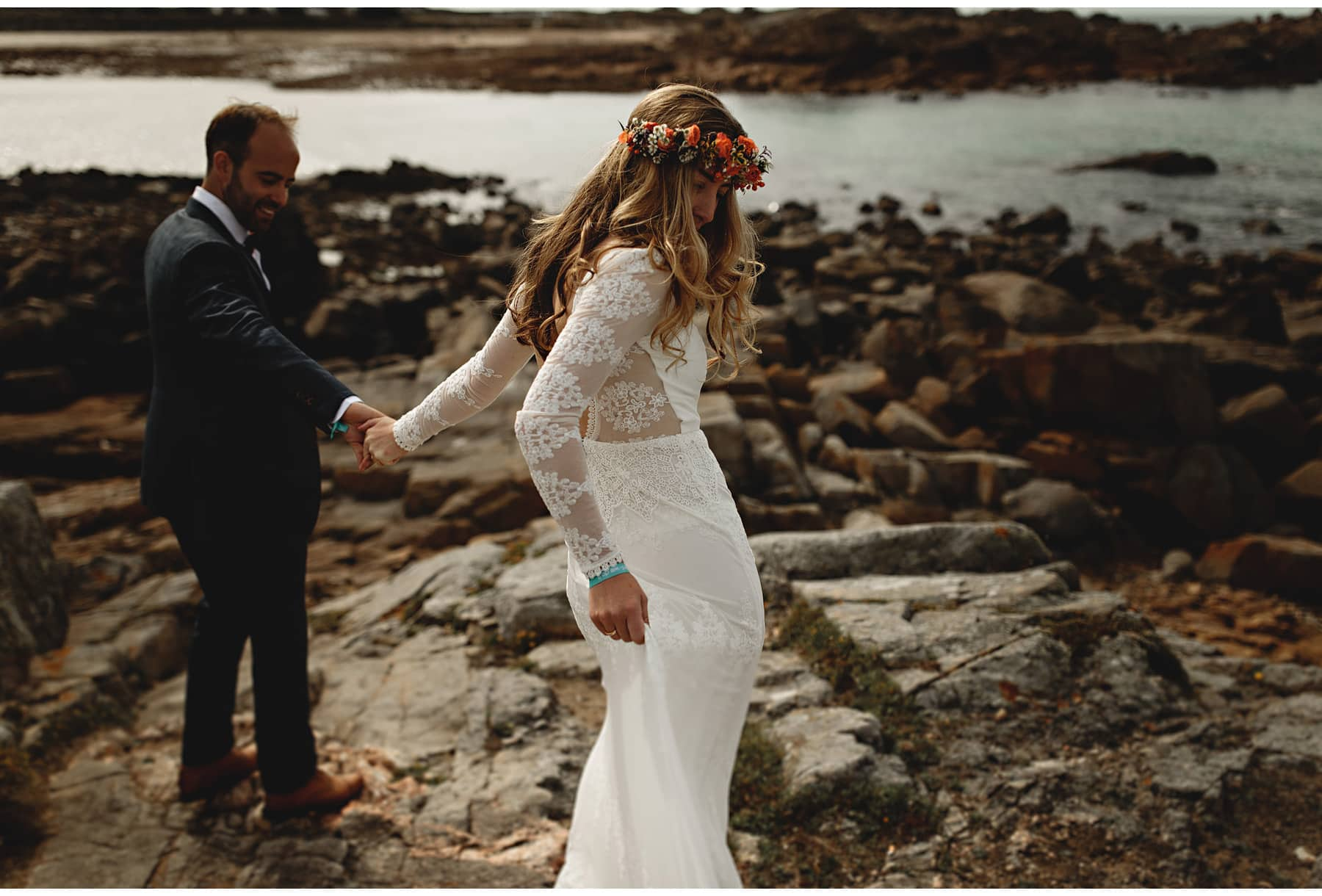 the bride and groom walking on the rocks on Jersey in thier wedding dress and suit