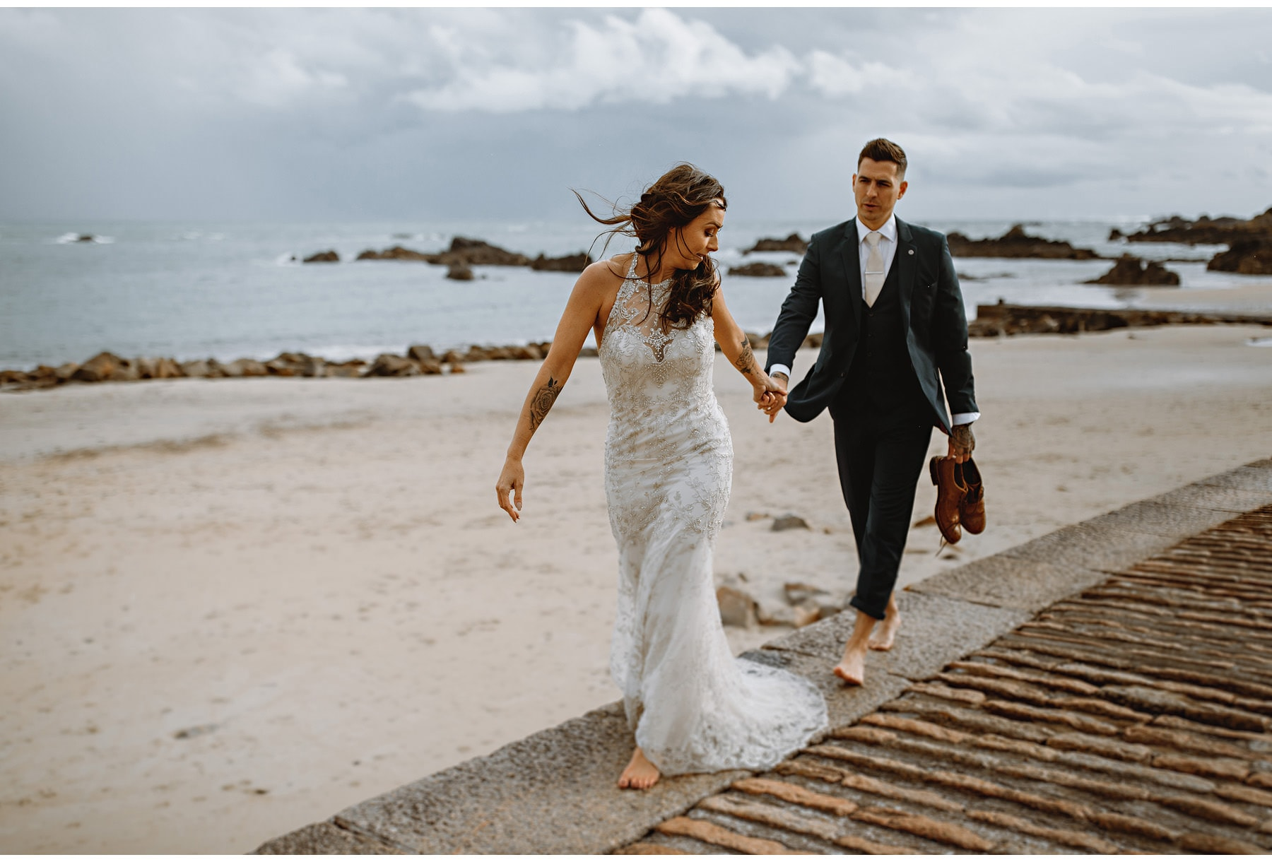 the bride and groom holding hands on the beach as they walk together