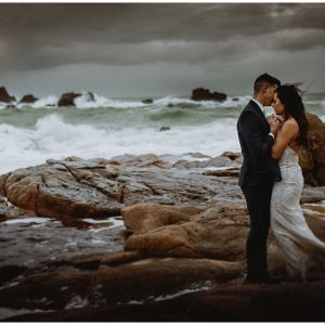bride and groom on the wild rocks at Corbierre lighthouse on Jersey
