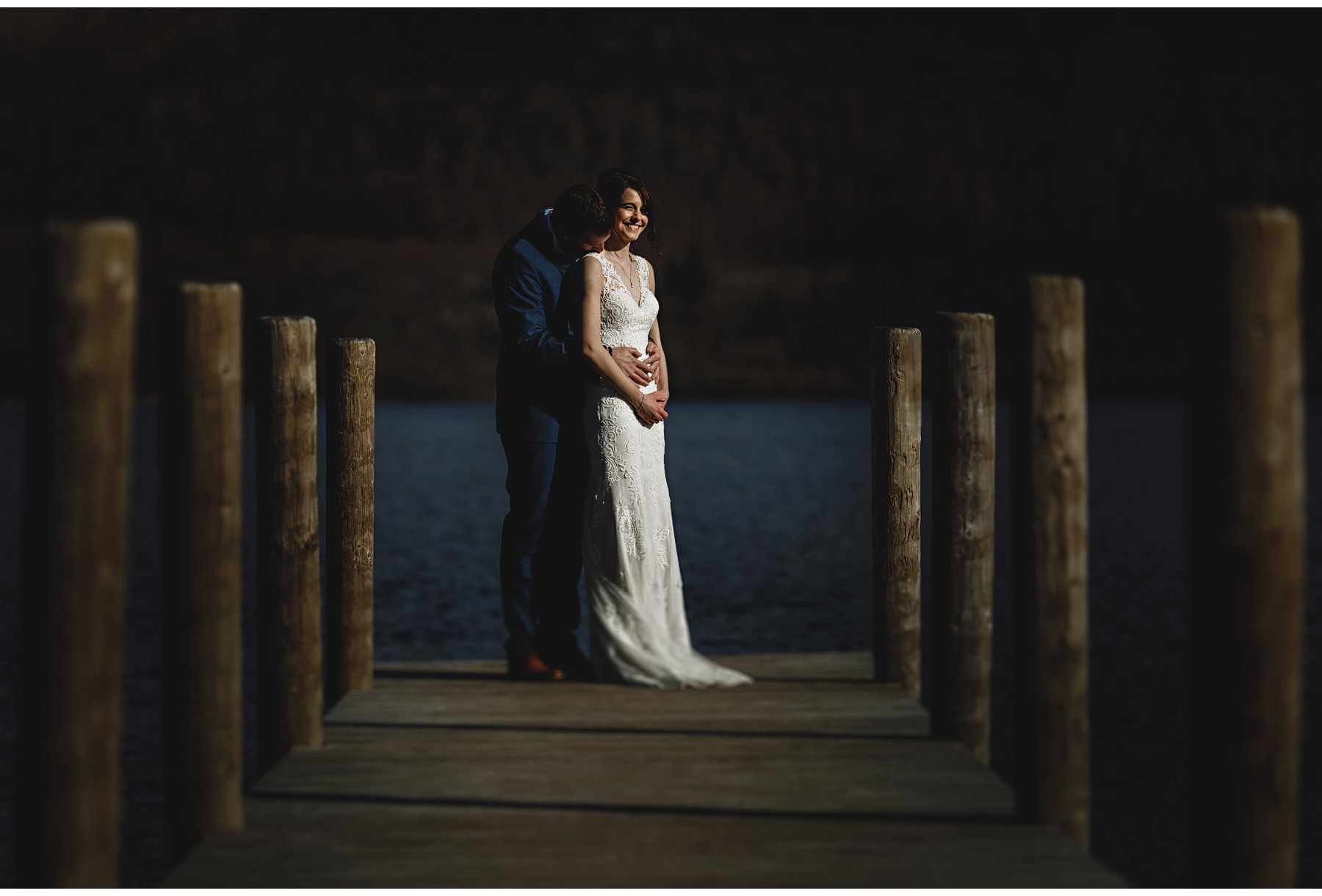 The bride & groom standing on a jetty on Coniston Water