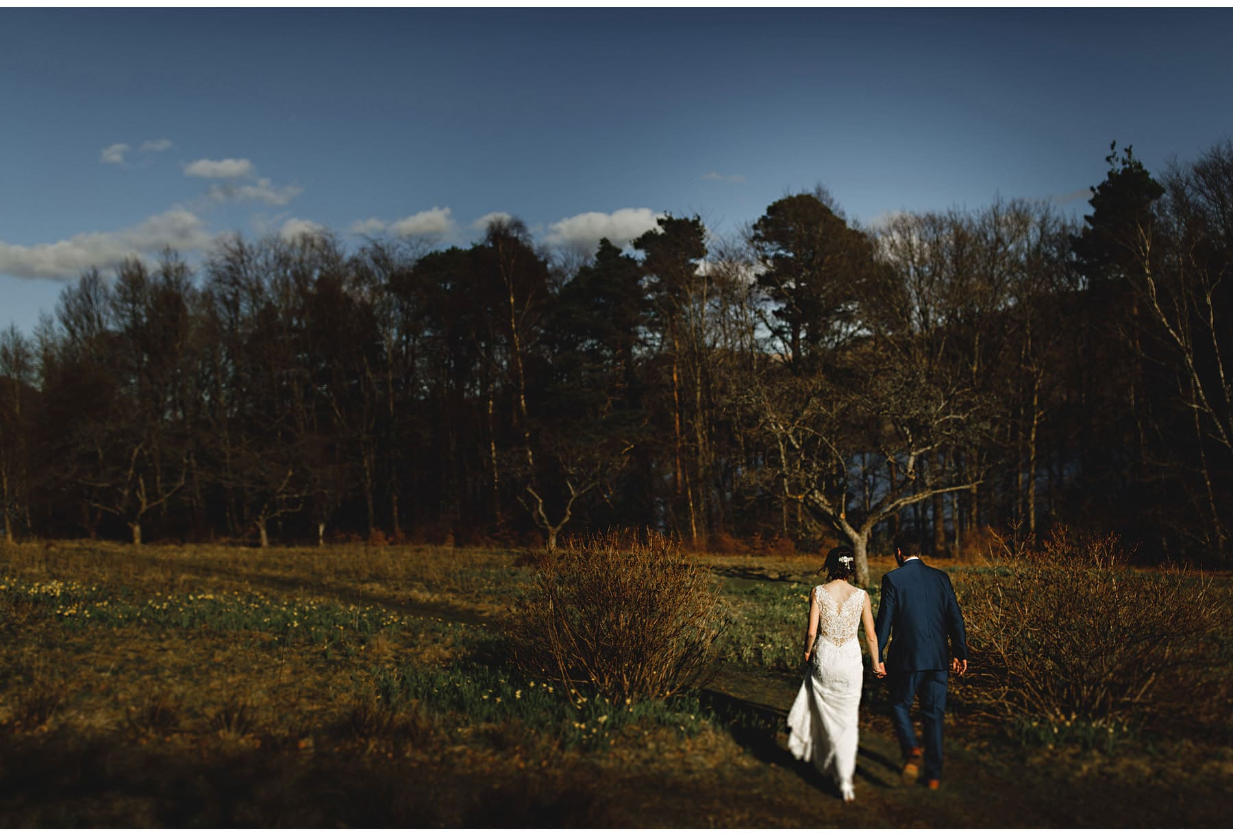 The bride & groom walking in the woods in the lake district
