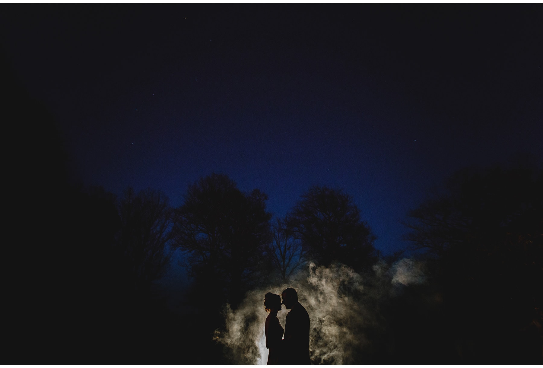 The bride & groom in silhouette against the mist