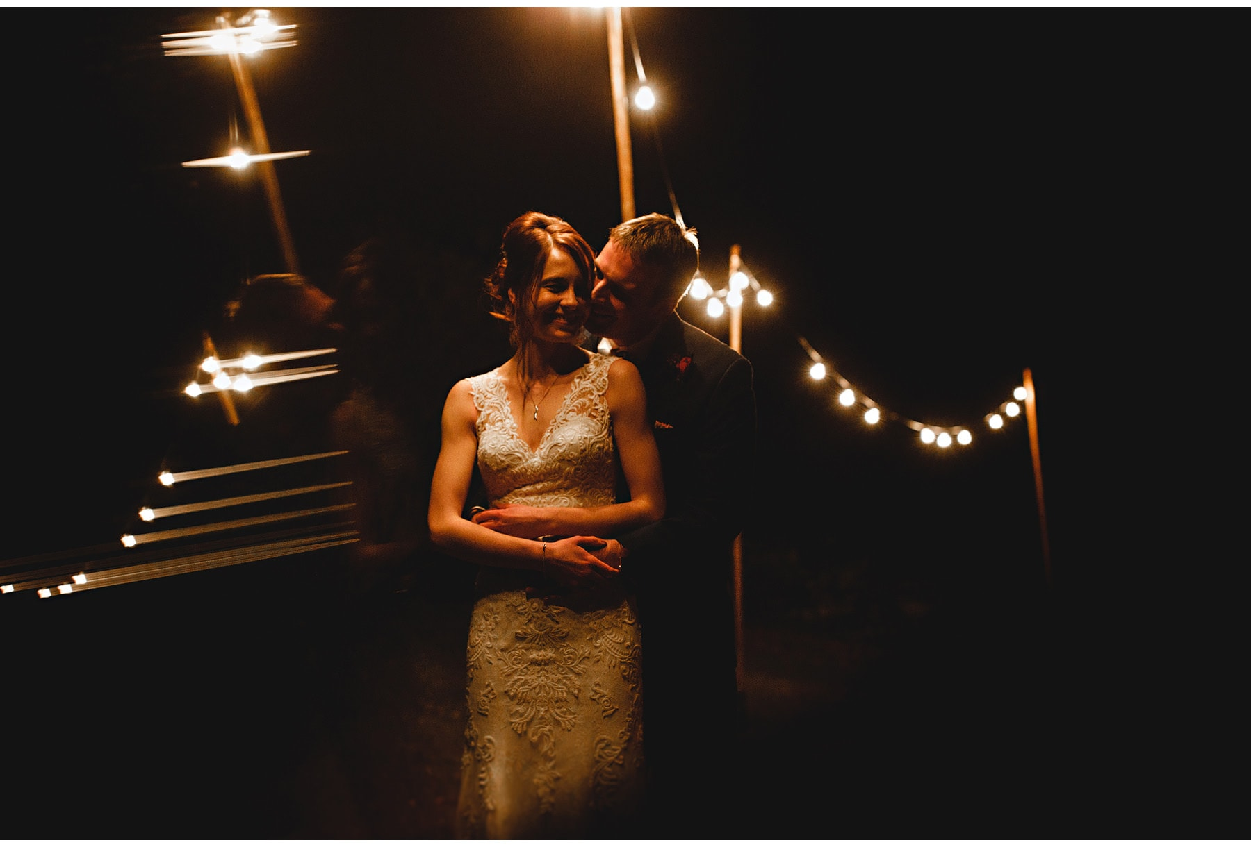 The bride & groom with festoon lights in the background