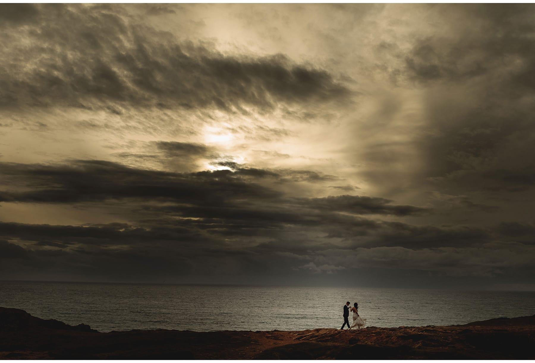 The bride & groom walking by the water