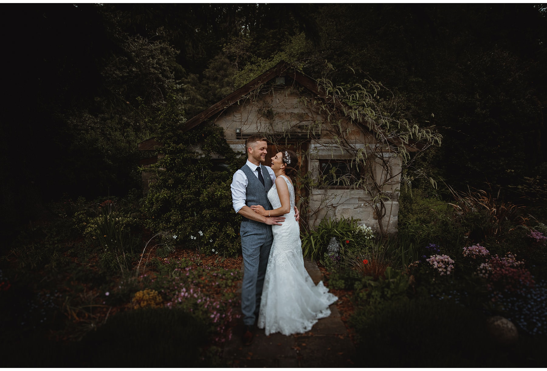 the bride & groom by the garden shed at Stancliffe Hall