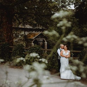 The bride and groom by the old saw mill at Osmaston Park in Derbyshire on their wedding day