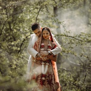 Our indian bride and groom in red outsite in the woods at Ladywood Estate