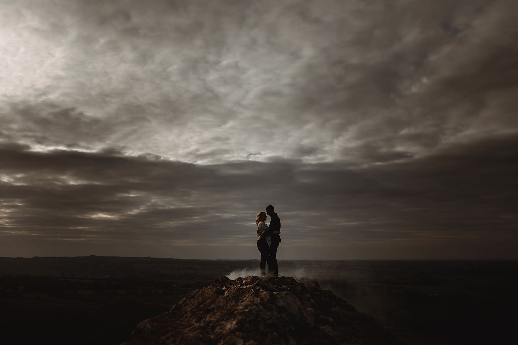 a wedding couple stood at the top of a mountiant surrounded by mist in derbyshire