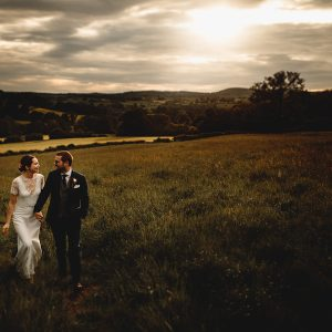 the bride and groom walking in golden sunset at their derbyshire wedding
