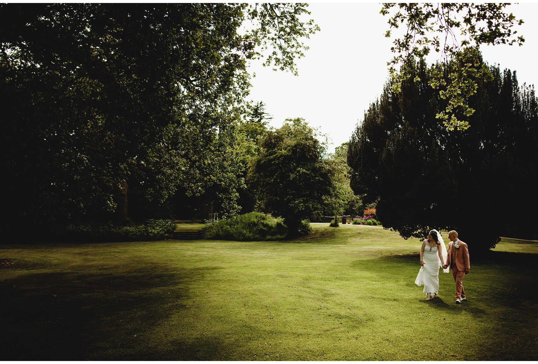 the bride & groom walking in the gardens at Hothorpe Hall