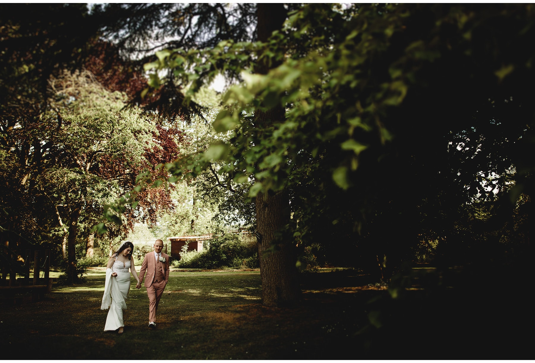 the bride & groom under the trees at Hothorpe Hall