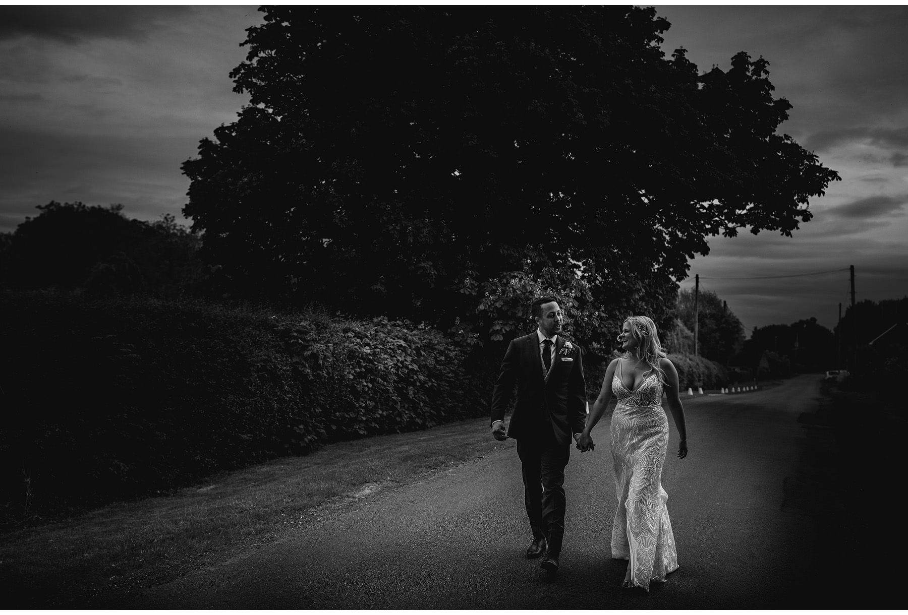 The bride & groom walking along the road