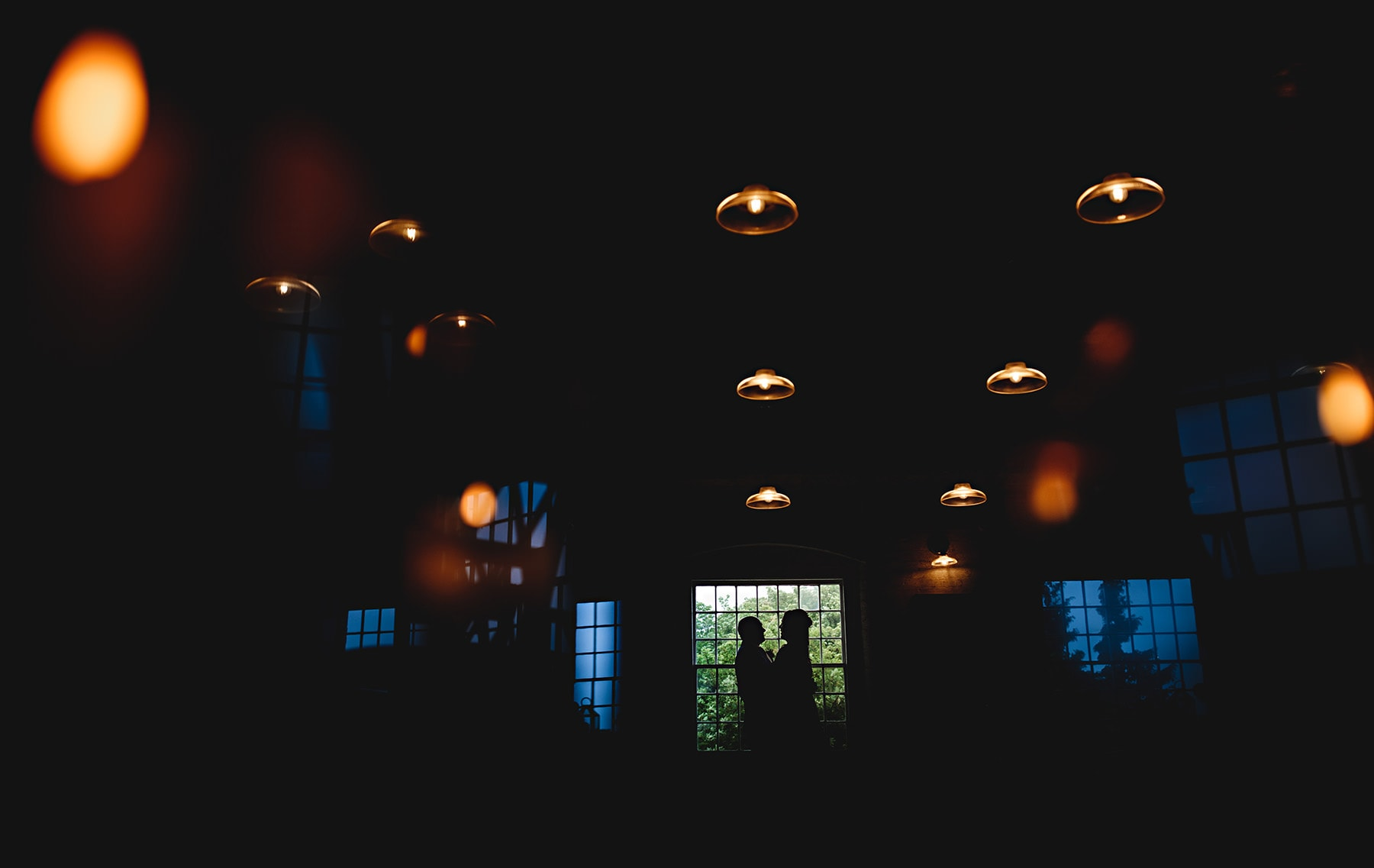 The bride and groom in shilouette against orange and blue lights at The West Mill in Derbyshire