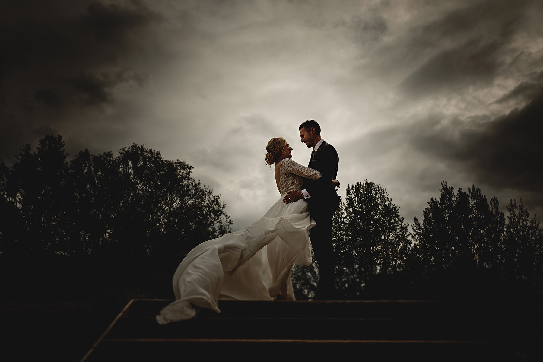 the bride and groom stood in dramatic light at The West Mill in Derbyshire on their wedding day