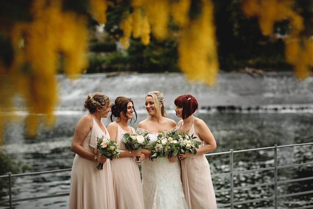bride and bridesmaids against yellow flowers by the river at the west mill wedding venue in derbyshire