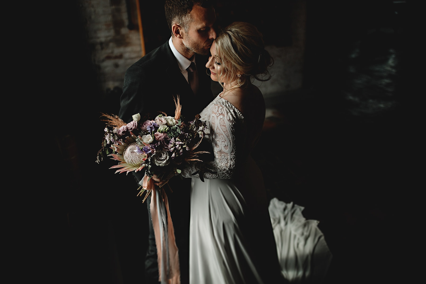 the bride and groom stood together holding beautiful flowers in dark light on their wedding day at the west mill in derbyshire