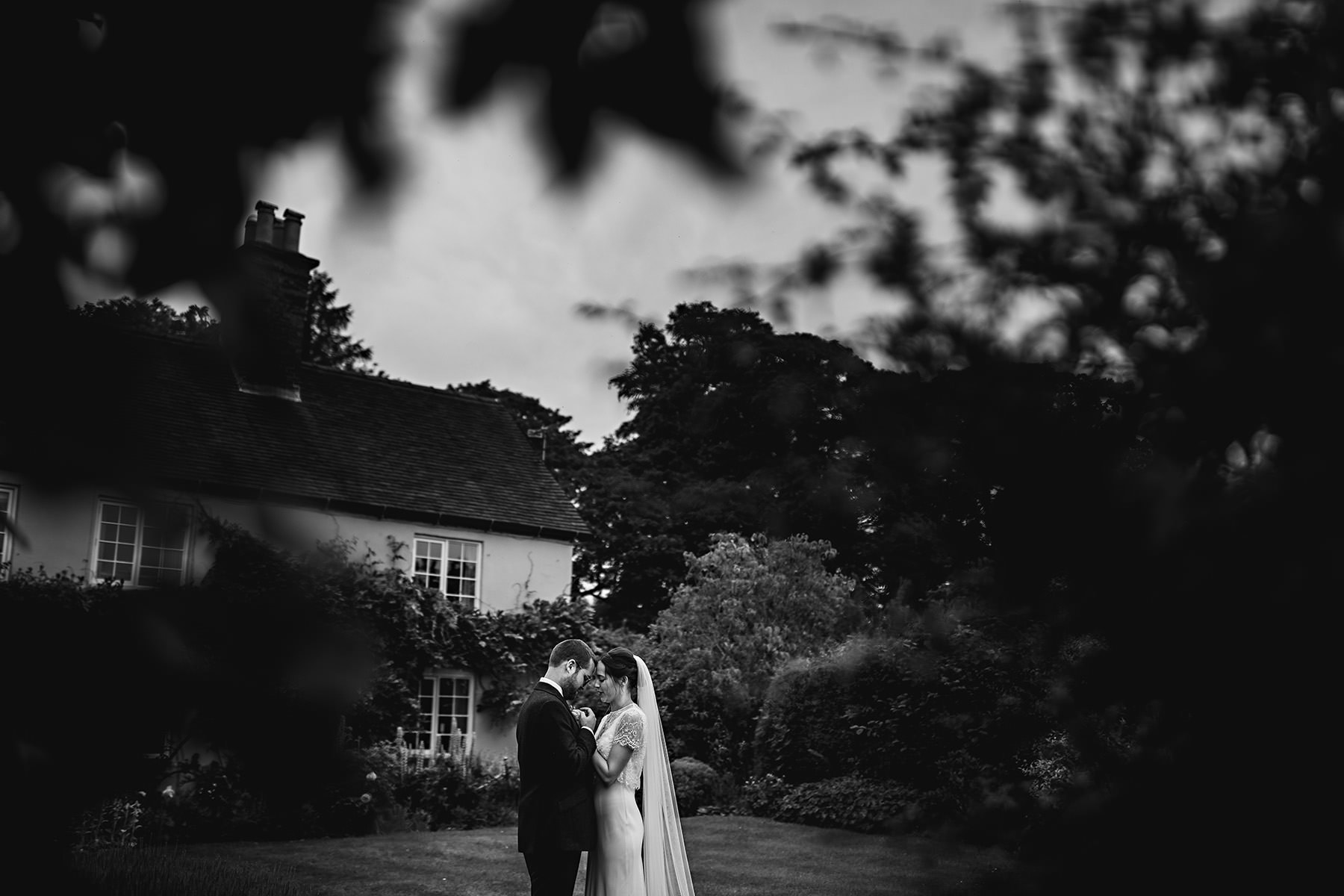 The bride and groom stood together in front of thier house in black and white monochrome