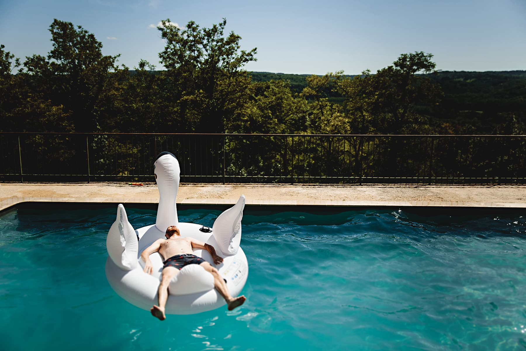 the groom sat in the blue swimmingpool in France at the Chateau Cazenec