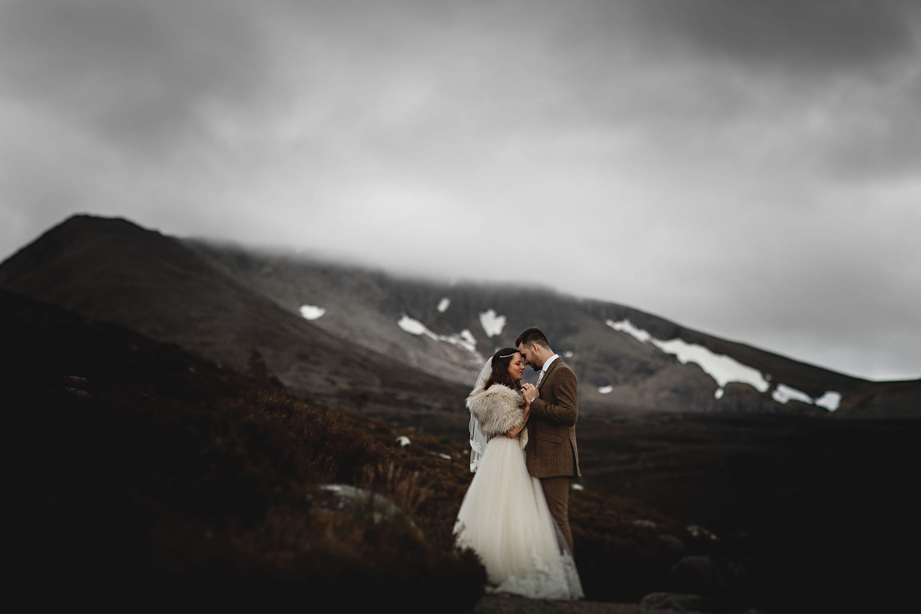 the bride and groom stood together in the scottish mountiant with snow behind them