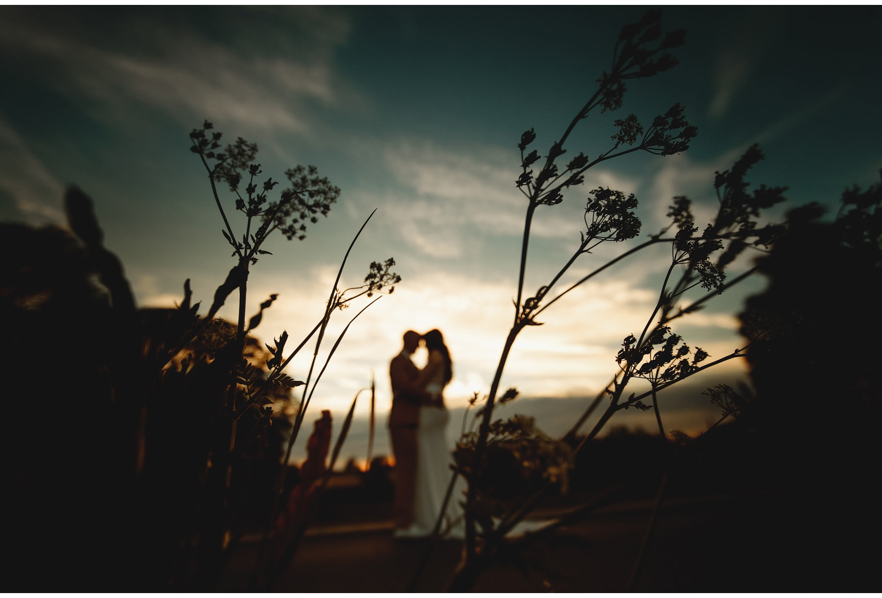 the bride & groom against the evening sky