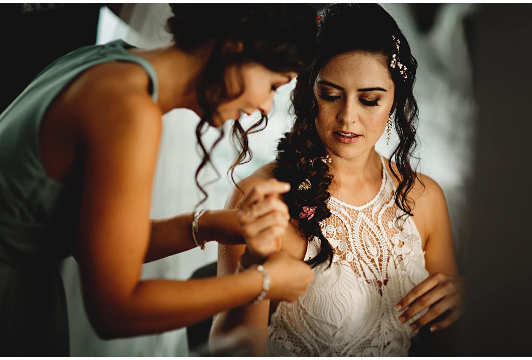 bridesmaid putting bracelet on bride