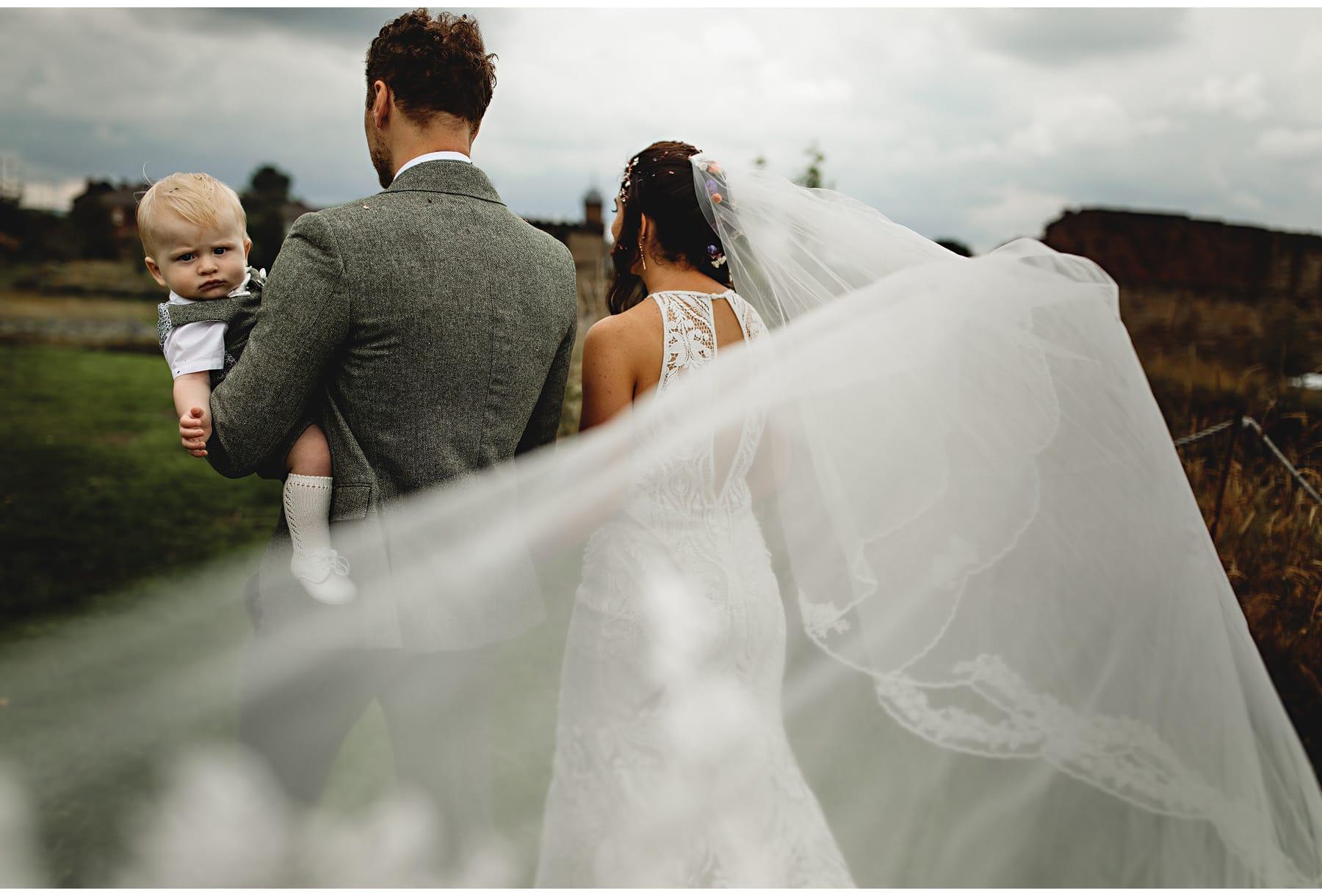 the bride & groom walking through the veil