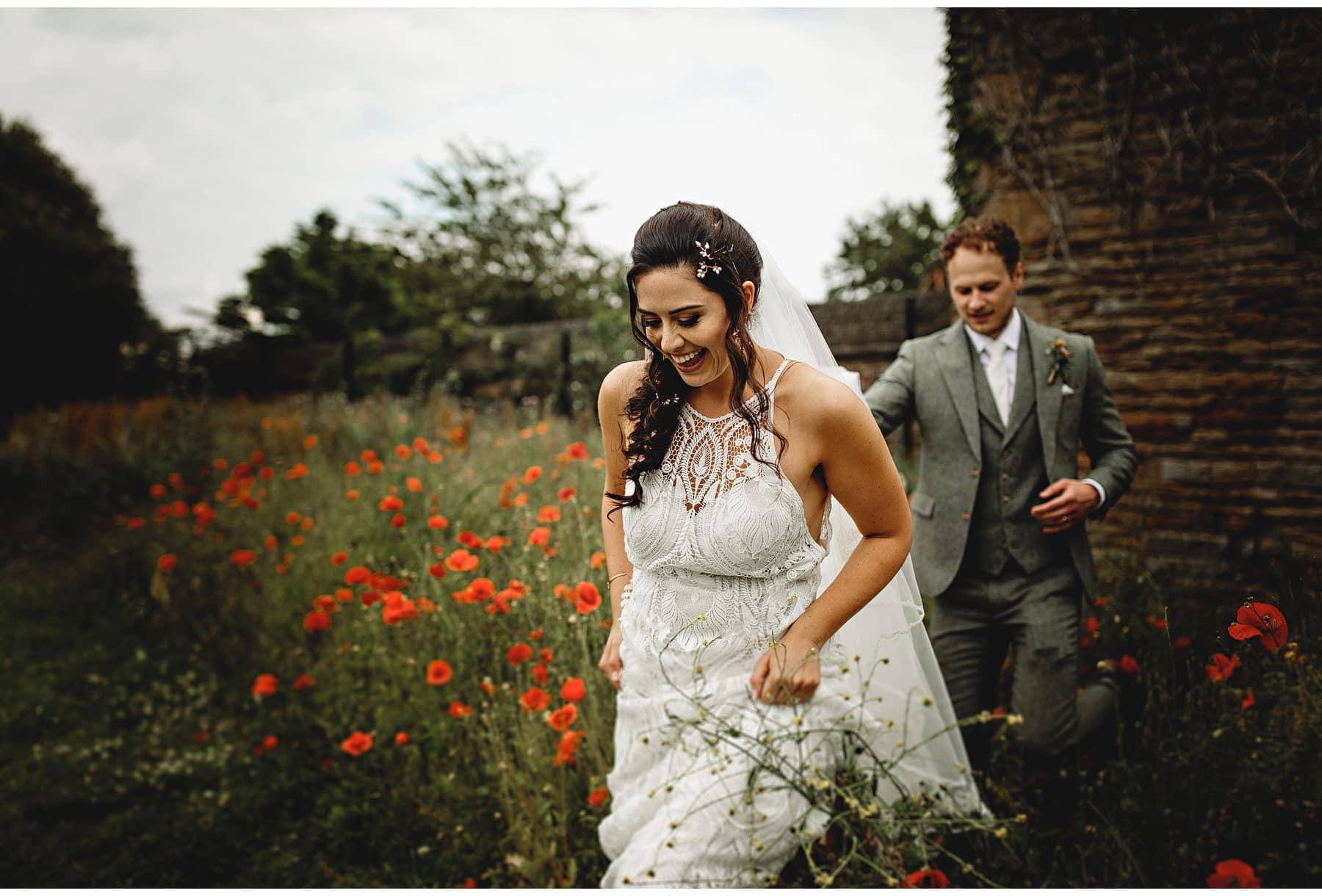 the bride & groom walking in the wild flowers