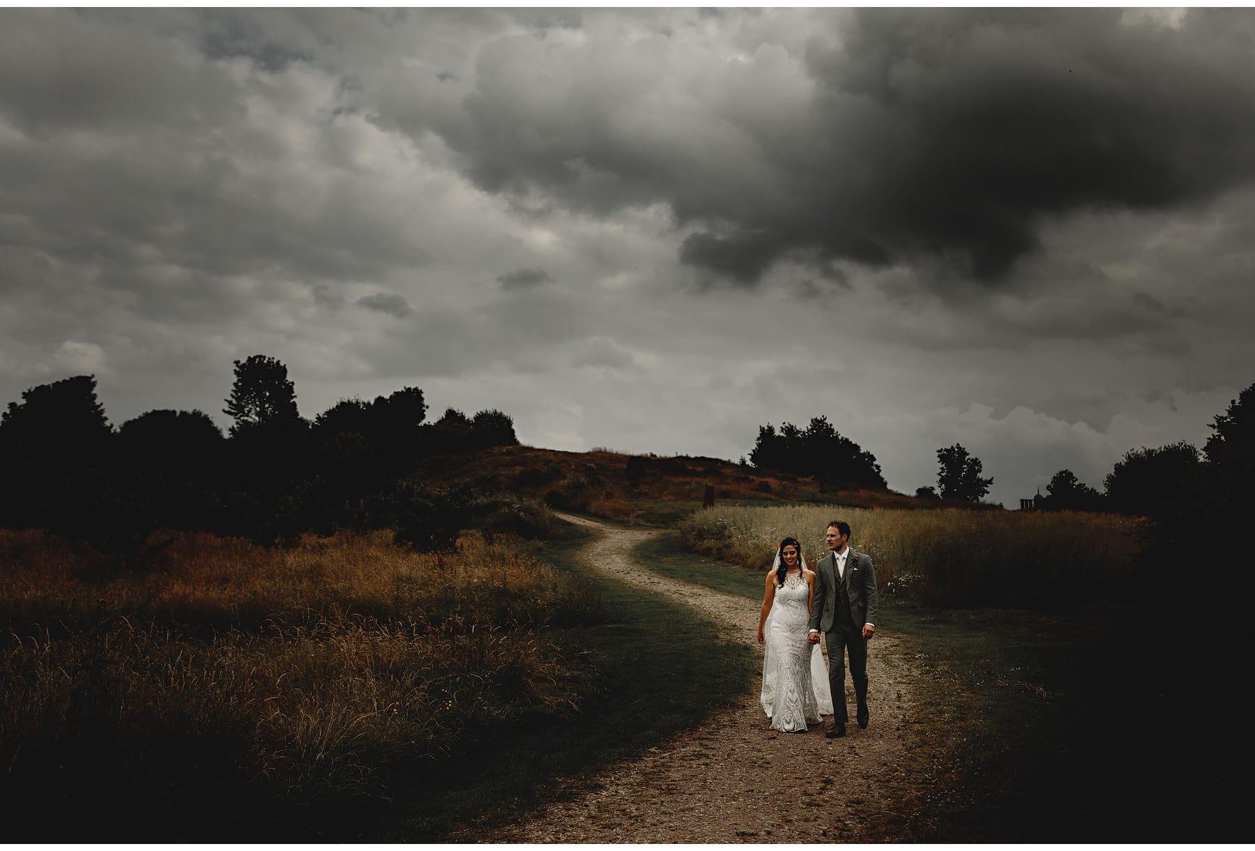 the bride & groom walking in the meadow