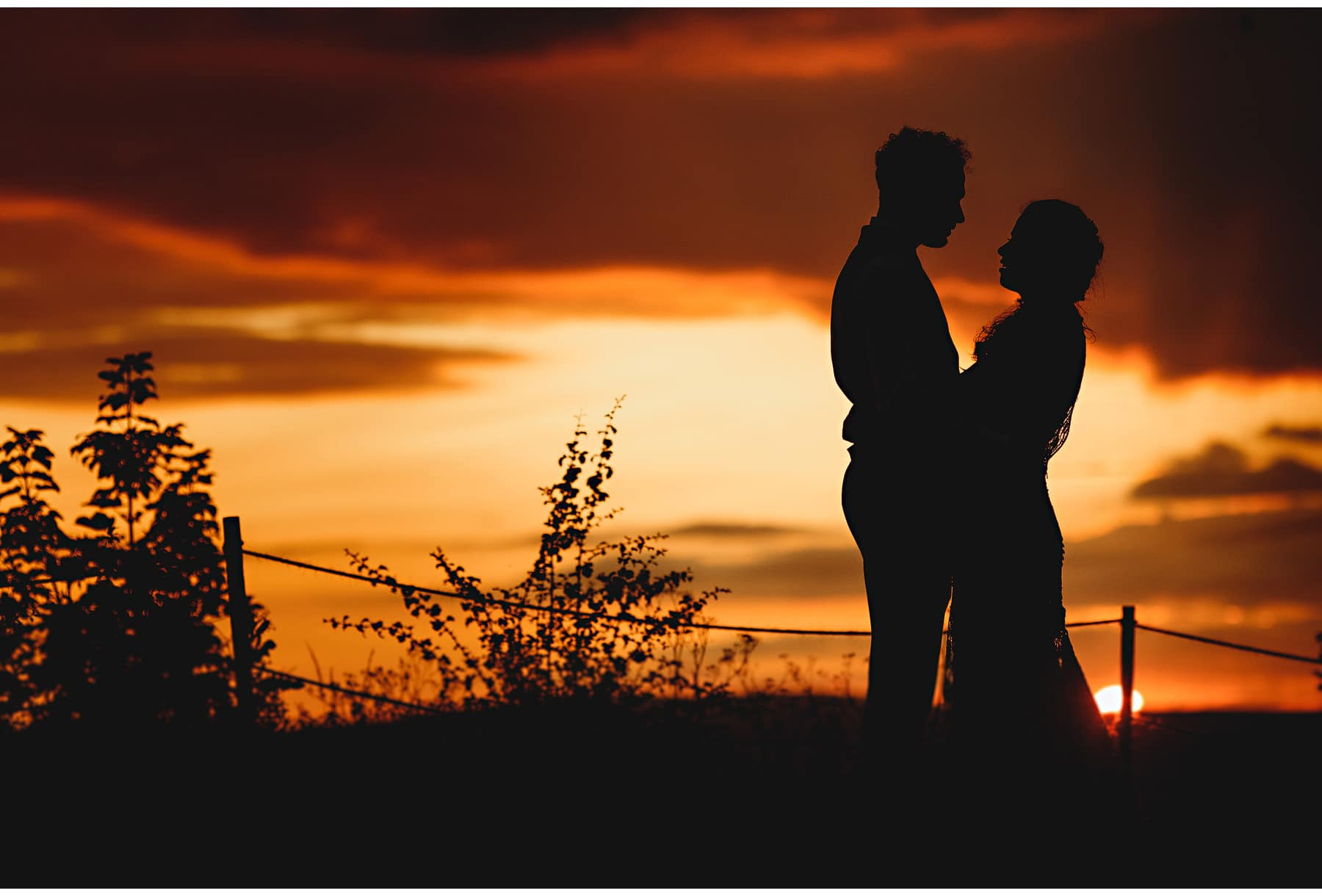 the bride & groom in silhouette at sunset