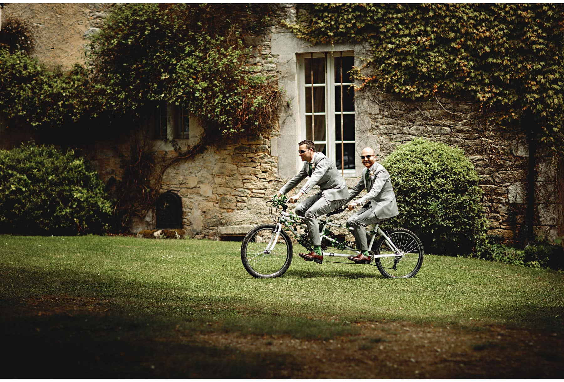 the groom & best man arriving on a tandem bicycle