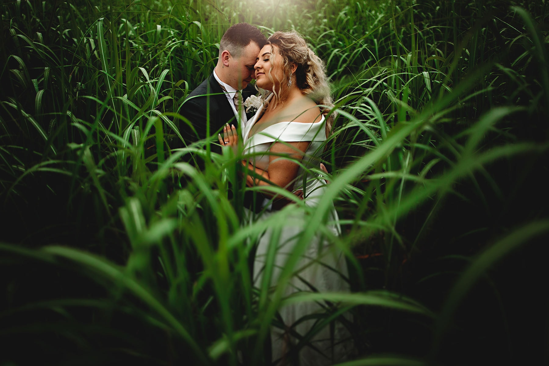 the bride and groom stood together in vivid green grass in a field at Alrewas hayes wedding venue
