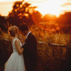 the bride and groom at golden hour in orange sunlight on thier wedding day at shustoke barns
