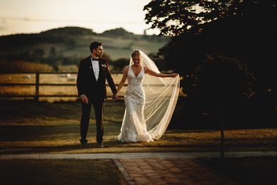 the bride and groom walking in golden sunshine at blackwell grange in the cotswolds on their wedding day