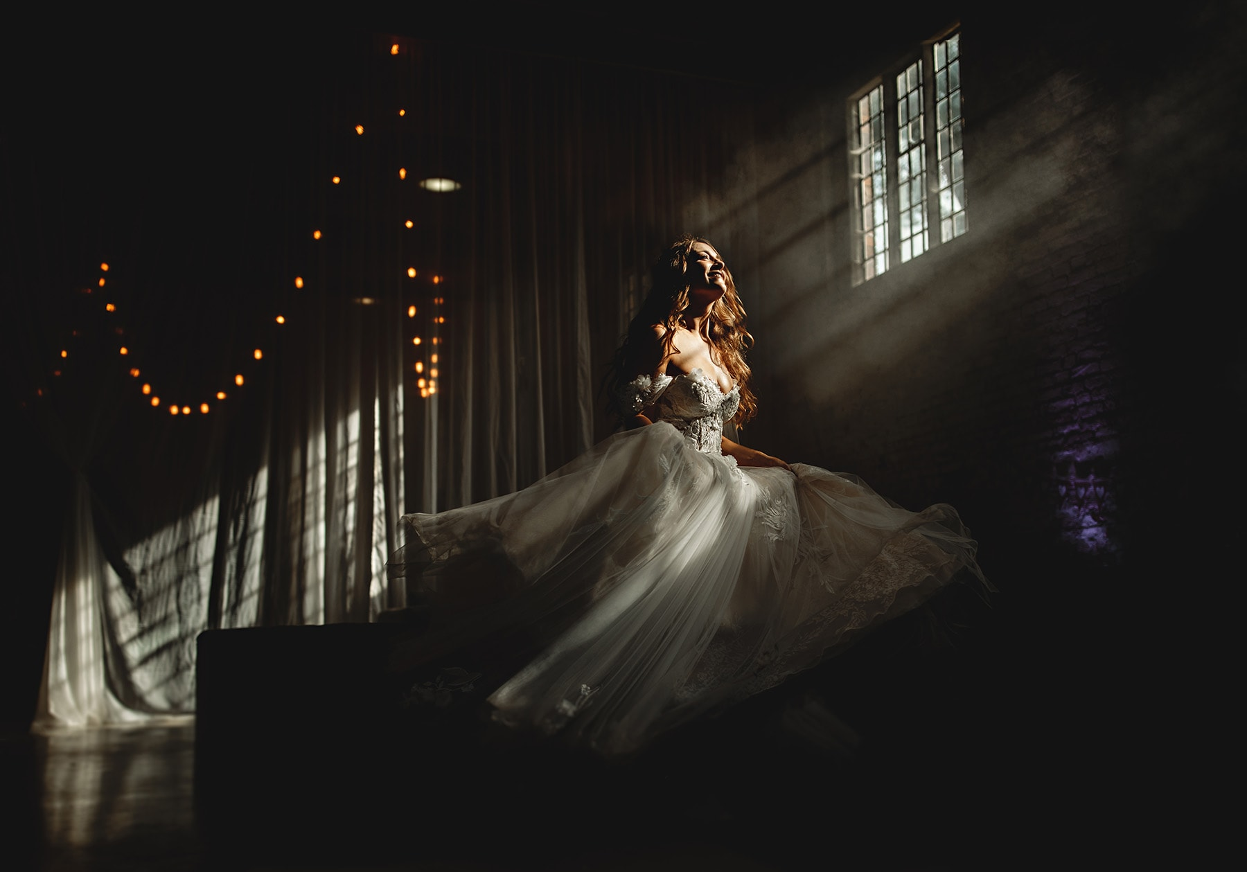 the bride spinning around in her wedding dress inside the riding school at calke abbey