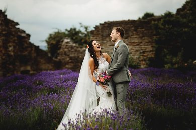 the bride and groom together laughing in amongst the purple lavender at Sheffield manor Lodge on their wedding day