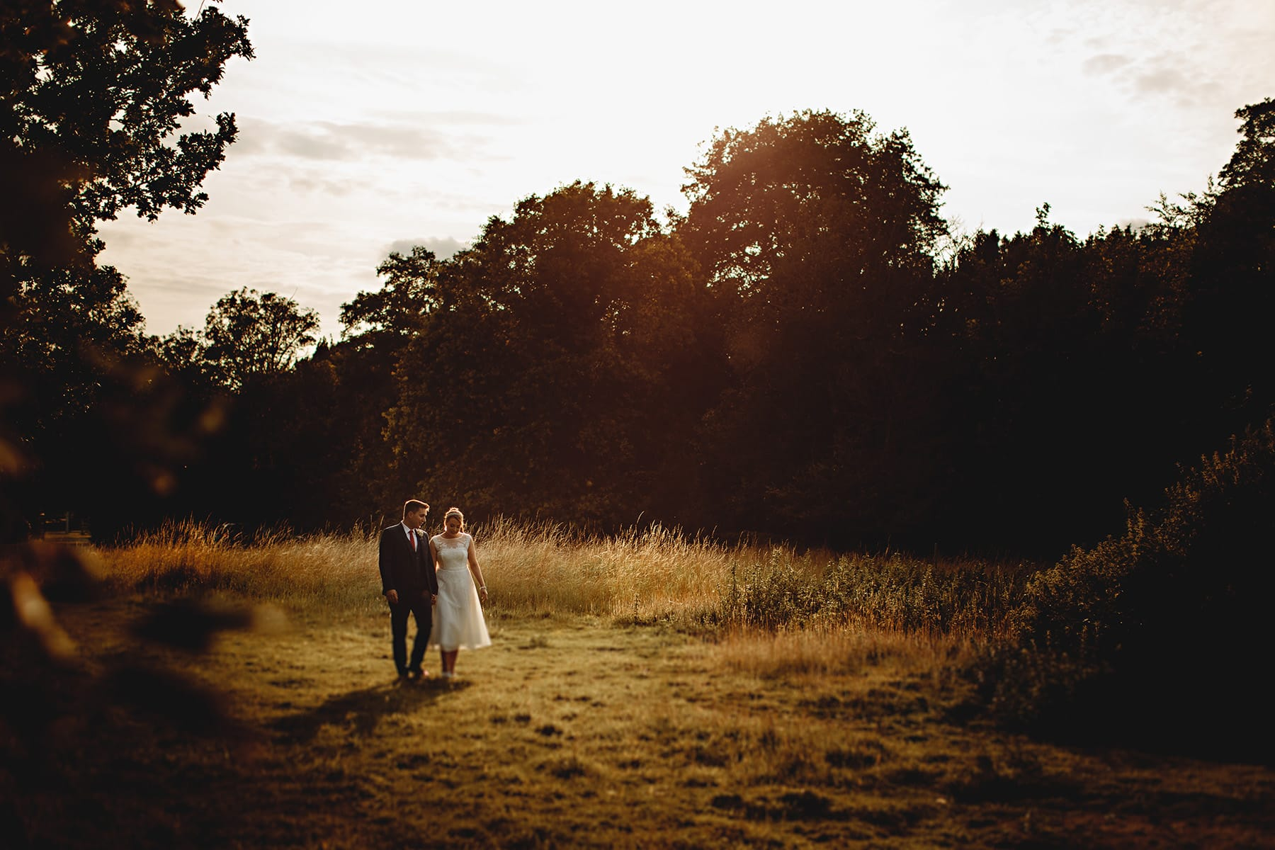 the bride and groom walking around in golden sunlinght on the Blankney Estate on their wedding day